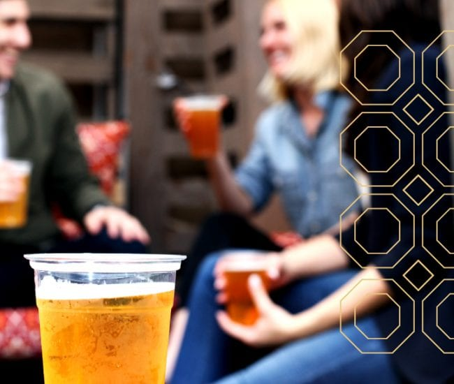 closeup of a cup of beer with blurred couple in background and gold octagon pattern overlay