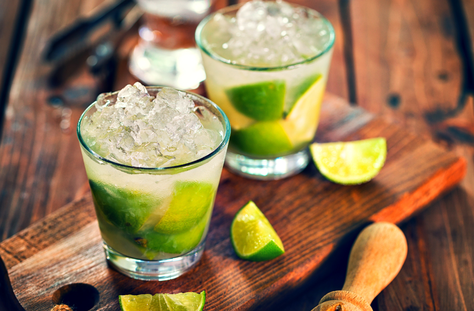 close up photo of two margaritas in small rocks glasses and lime slices on the side