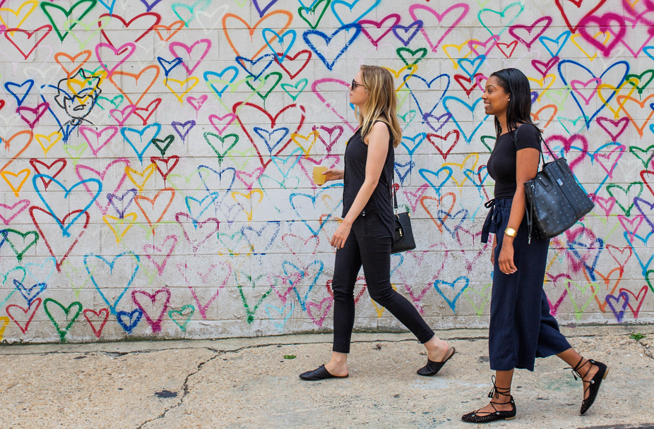 two women walking on sidewalk passing a wall with a mural of multicolored hearts