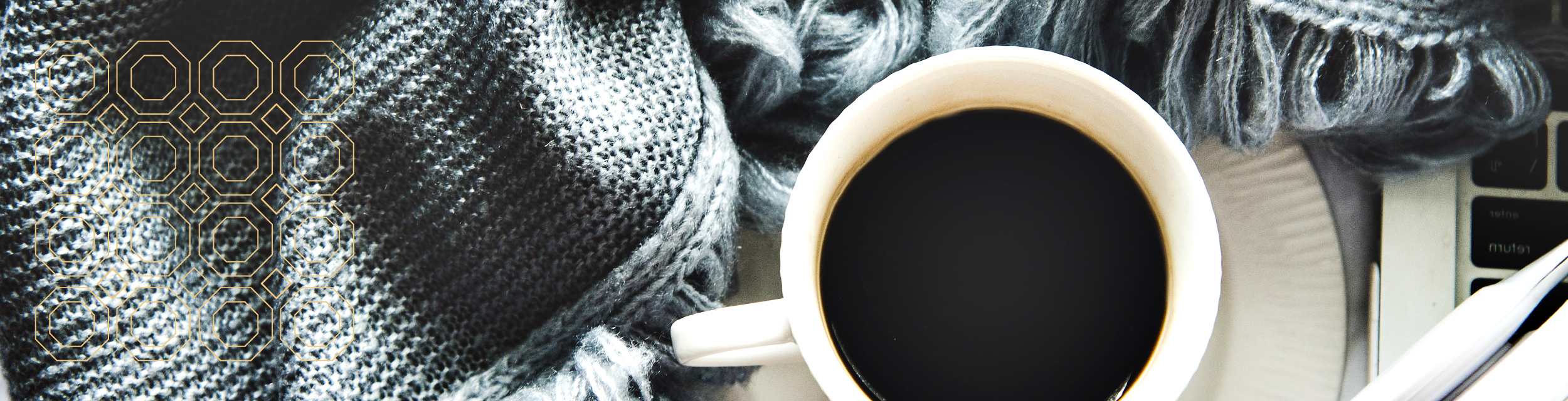 close up of a full coffee cup on saucer surrounded by gray/blue blanket