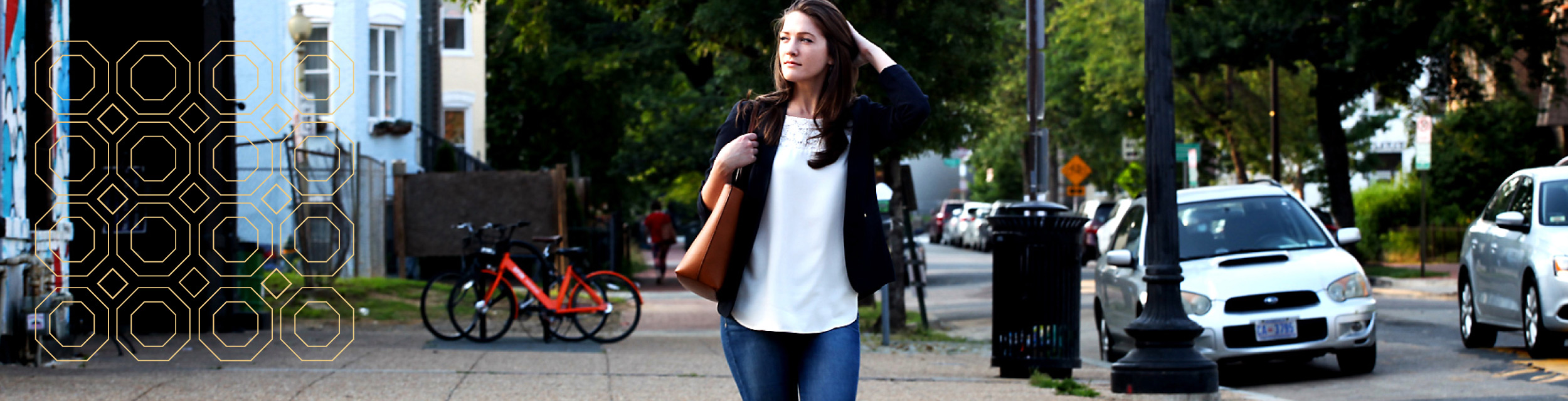 woman in white shirt, jeans and a brown jacket holding a leather bag and walking down a city sidewalk