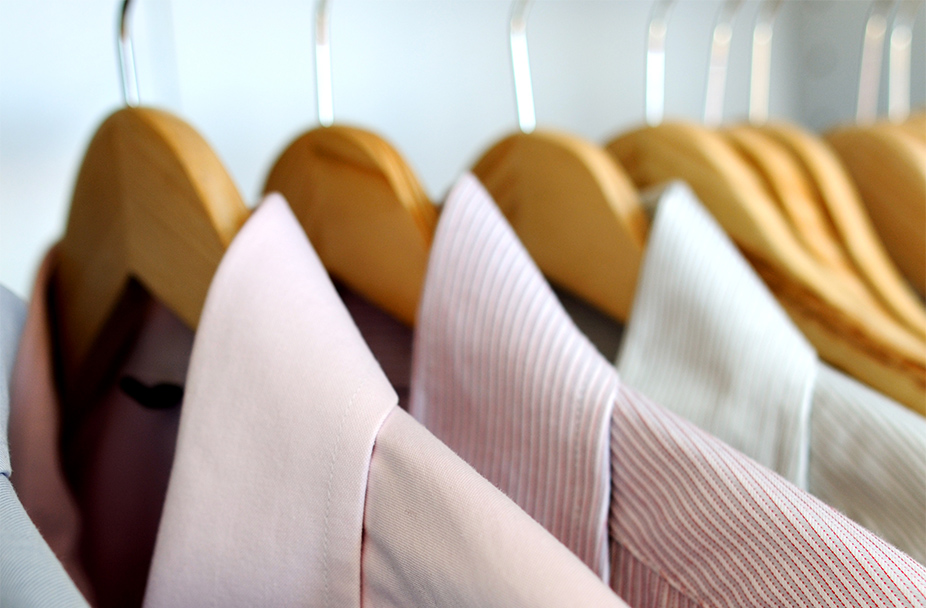 variety of pink, red and white dress shirts on hangers in closet