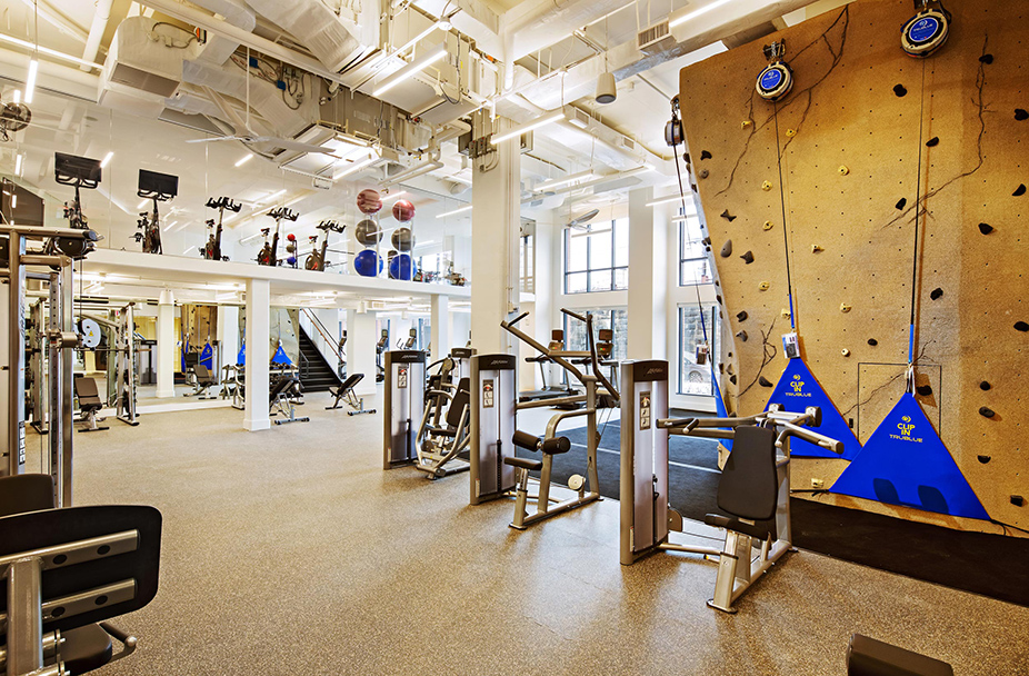 Union Place fitness center with rock climbing wall, weight machines, stationary bikes, and treadmills