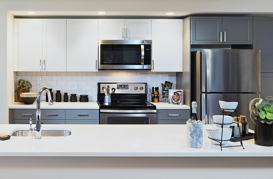 Kitchen at Union Place with island; gray/white cabinets; white countertops; and stainless steel appliances
